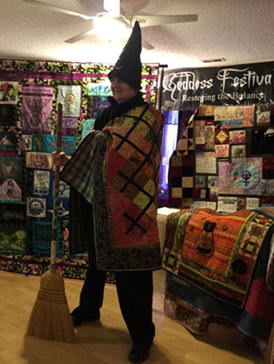 Paula in a pointed witch's hat with many of her political quilts behind her.